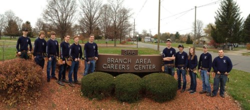 students posing at BACC sign with electrical tools