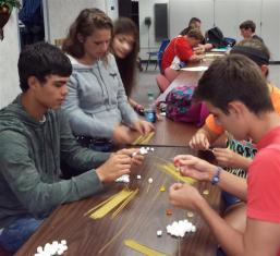 students working with spaghetti at a table