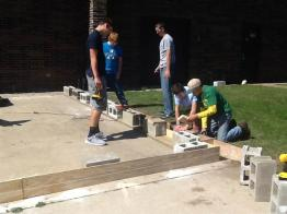 students laying concrete blocks