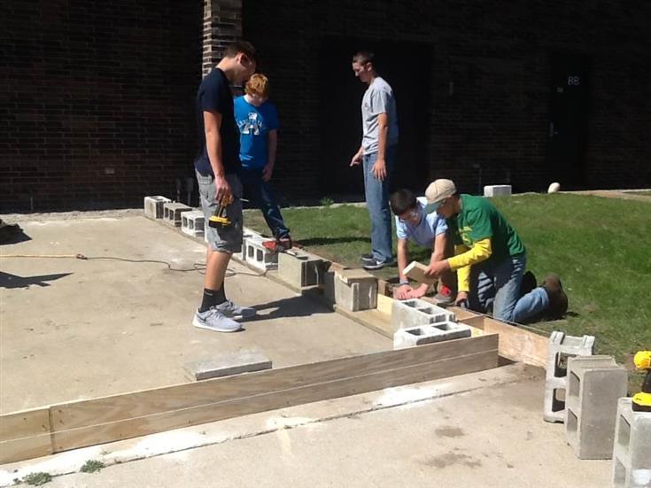 students laying concrete blocks