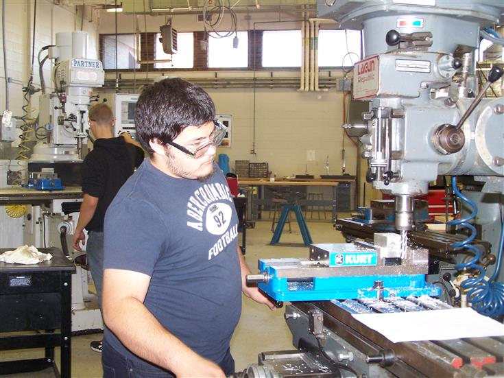 student operating a milling machine