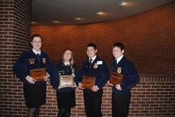 4 students posing with plaques