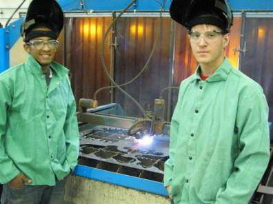 students posing with a robotic cutting torch