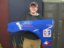 student holding blue fender with Ford logo