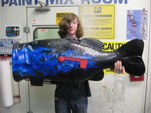 student holding airbrushed fish mailbox
