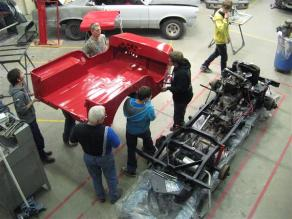 students carrying a jeep body