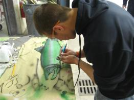student airbrushing a metal fish