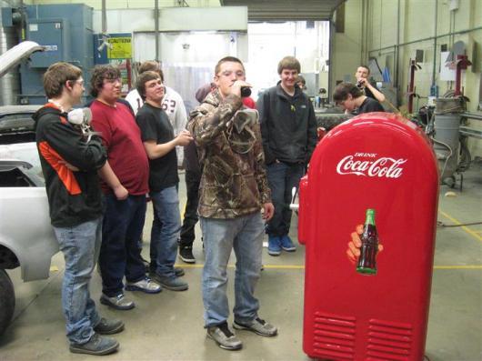 students admiring red coke machine