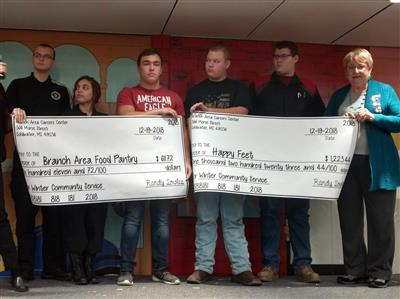 Students on the Winter Community Service committee at the Branch Area Careers Center present checks to Renate Brenneke, Branch Area Food Pantry representative, and Connie Winbigler, Altrusa International member, Wednesday, December 19, 2018 at their winter assembly.