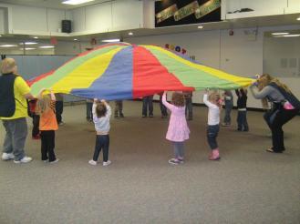 Students raising a colerful parachute