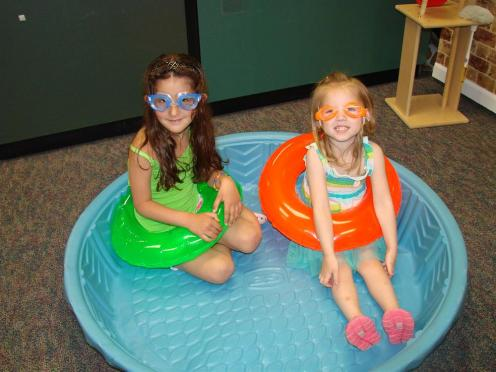 2 girls sitting in kiddy pool
