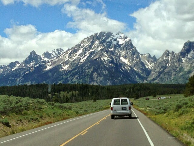 White van approaching the Grand Teton MOuntains