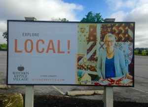 Picture of a bill board promoting the brand of the Kitchen Kettle Village and buying local.