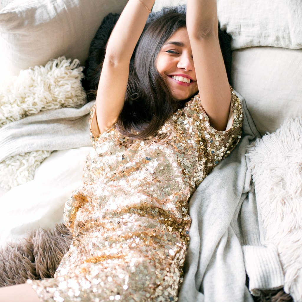 woman wearing brown sequin dress laying on the bed 698864