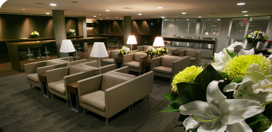 Brown lounge seats with white flowers in the Porter lounge at Billy Bishop Airport