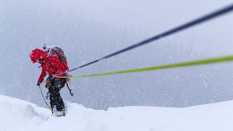 A rock climber wearing an Arc'terx brand jacket climbing up a rope in a snow storm