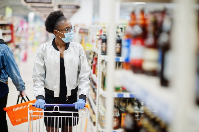 WORLD BANK GLOBAL ECONOMY African woman wearing disposable medical mask and gloves shopping in supermarket during coronavirus pandemia outbreak. Epidemic time.