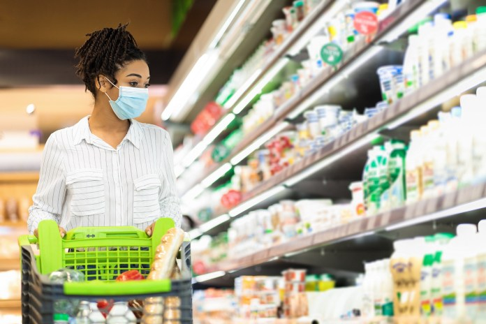 African Lady Wearing Face Mask Buying Food In Supermarket