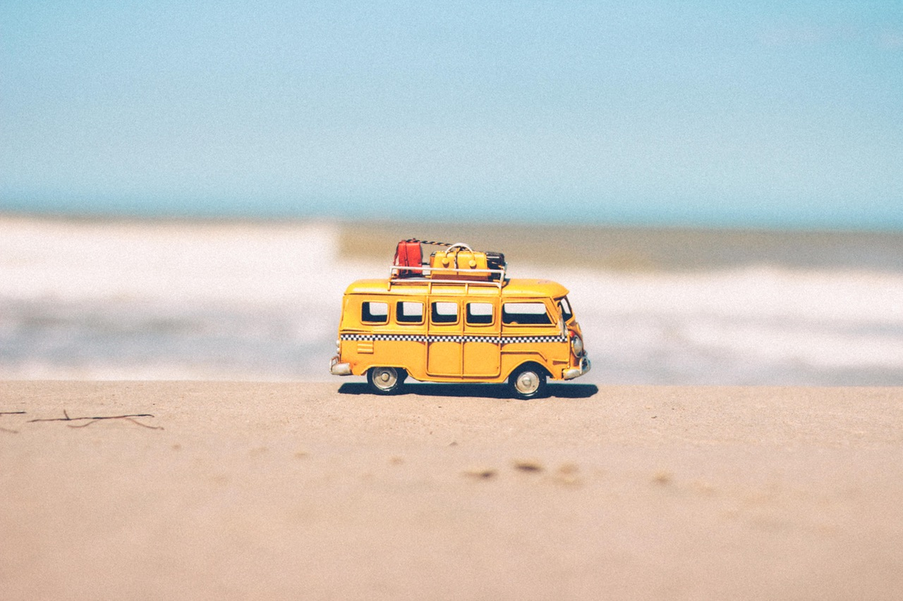 Toy VW bus on the beach, ready for summer fun