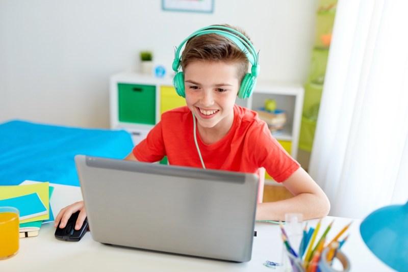 Aluno de escola bilíngue estudando no computador.