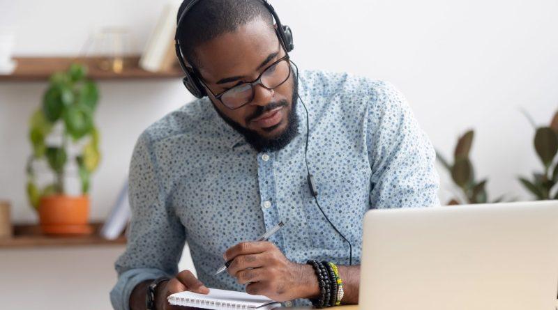 Jovem com fones de ouvido e bloco de notas, em frente ao computador, aprendendo inglês