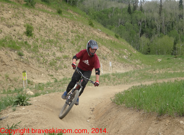 a boy turning on a steep curve on the Rustler Ridge downhill bike trail in the steamboat colorado bike park