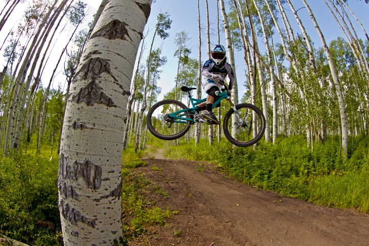 a pro downhill bike rider jumping sideways in the trail at Bike Snowmass near Aspen Colorado