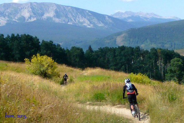 a family downhill biking in the evolution bike park near crested butte, colorado