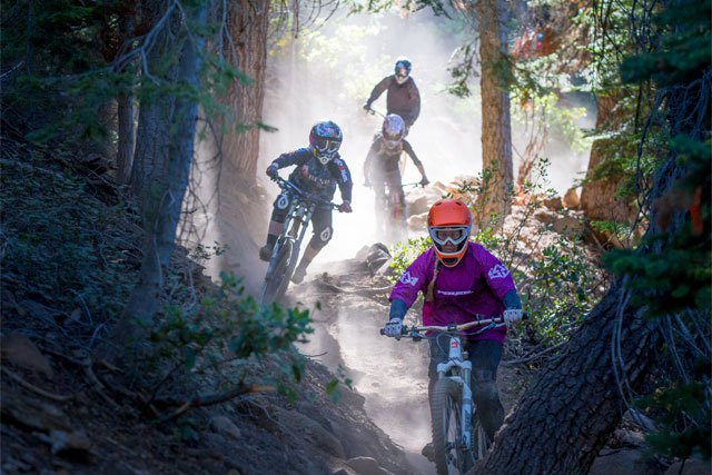 a group of women downhill bikers riding a trail through the forest at northstar resort california