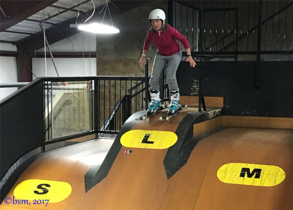 brave ski mom skiing down the small jump to foam in the barn at woodward copper