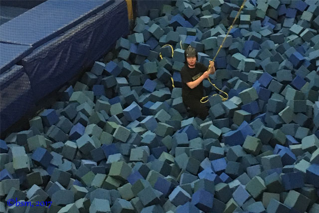 climbing a rope to climb out of the largest foam pit after a ski jump in the barn at woodward copper