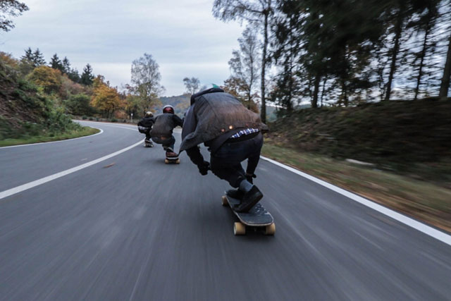mountain longboarders riding down a mountain road