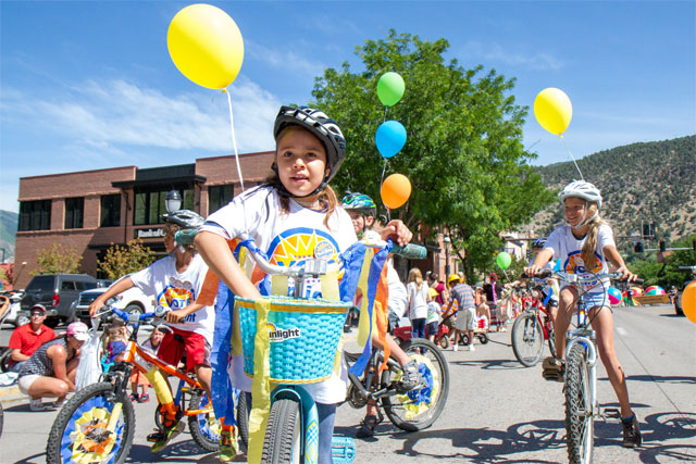 sunlight mini mayors riding bikes in strawberry days parade in glenwood springs colorado