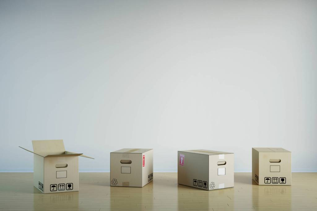 Four moving boxes on a floor, the first one is open.