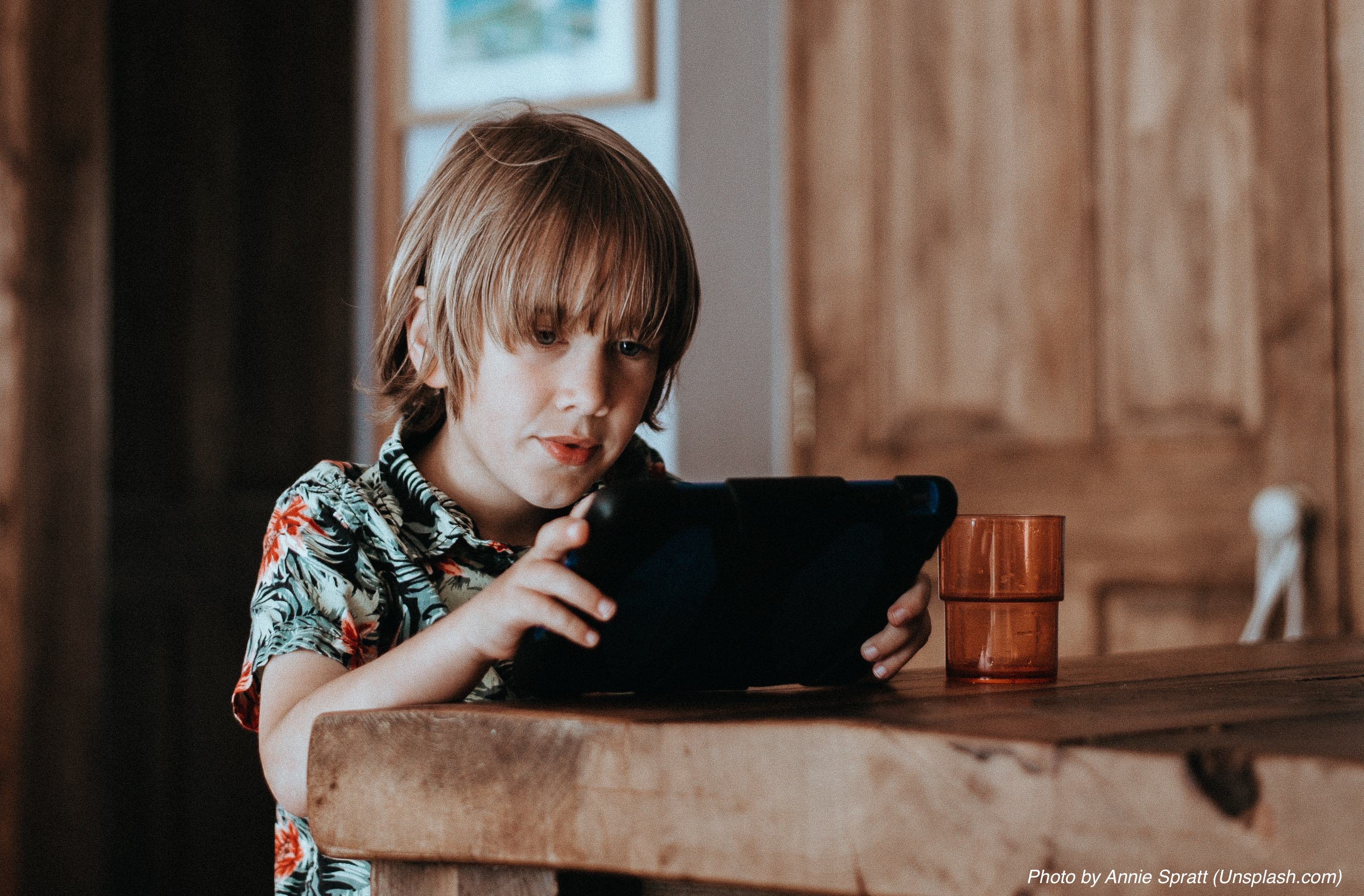 Child sitting at table using a tablet commputer