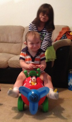 Sister pushing him on a car