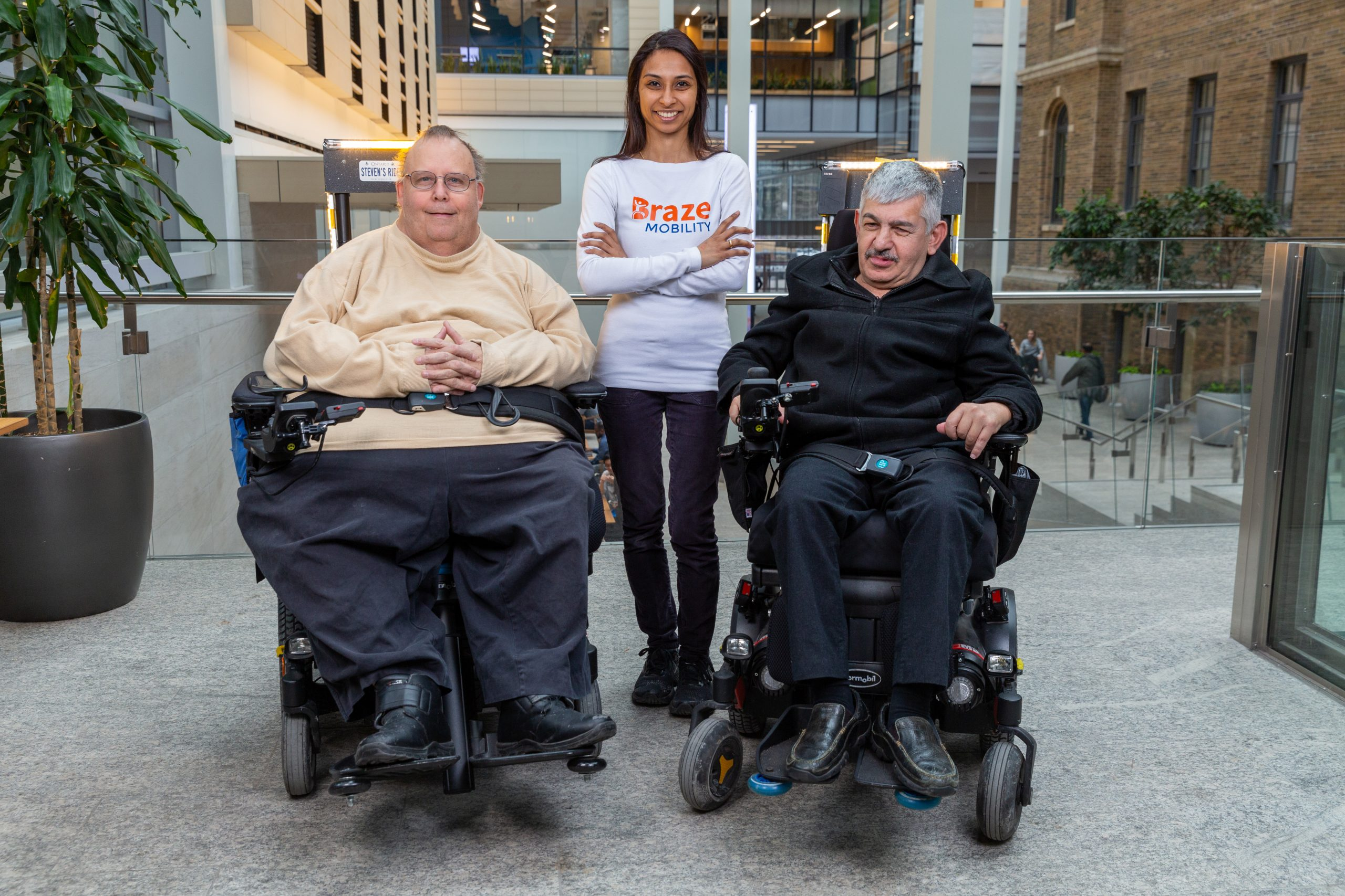 Photo of Pooja smiling with arms crossed wearing a white Braze Mobility long sleeved shirt with two customers in power wheelchairs