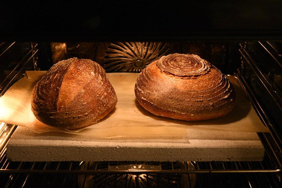 Painile cu maia Vermont Sourdough in timp ce sunt coapte in cuptor pe o placa de samota. Fiind supradospite, tăieturile nu s-au deschis foarte spectaculos.