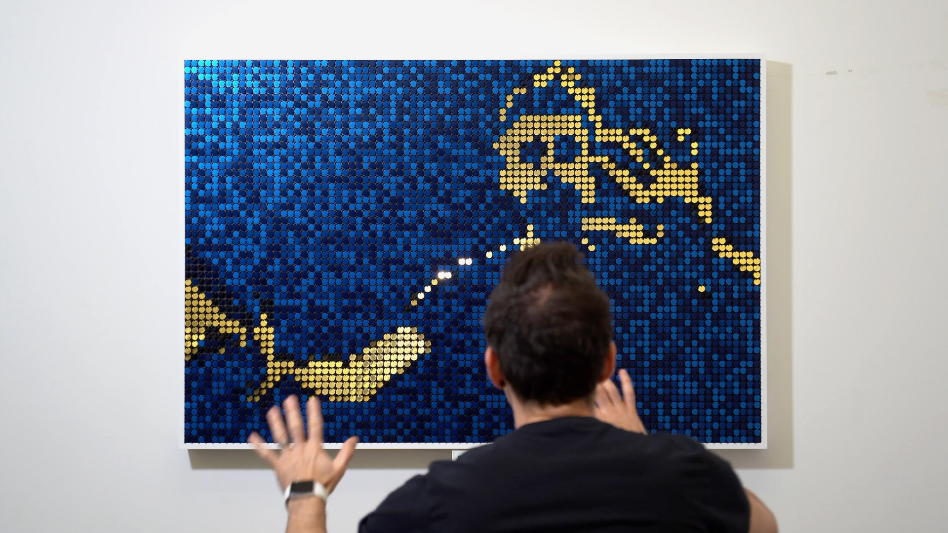 Person interacting with blue and gold Flip-Discs artwork called Seismic Echo. Created by BREAKFAST.