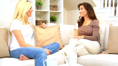 stock-footage-two-beautiful-girlfriends-chatting-at-home-with-a-cup-of-coffee