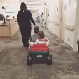 Our sweet nurse pulling my babies in the hospital's pediatric wagon after 10 hours of being there. They were getting restless.