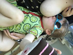 Toddler nursing with toy cake wearing sunglasses. Nursing boundaries