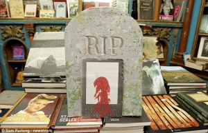 "Display of books with a tombstone and a ""bleeding"" Kindle"