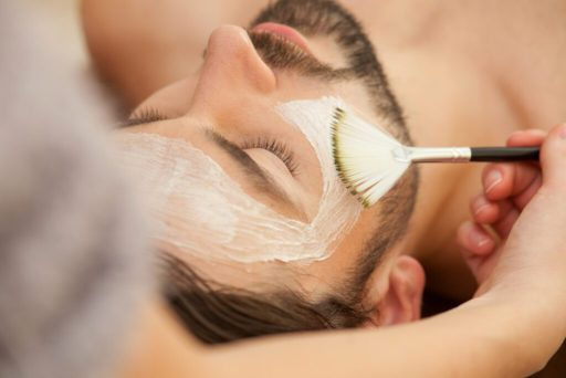 A man with pale skin and a beard and moustache is lying down while someone brushes cream onto his face during a facial.