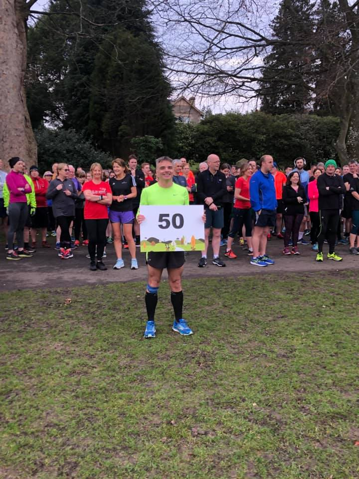 Ian looking sheepish whilst being made to pose for his milestone Parkrun