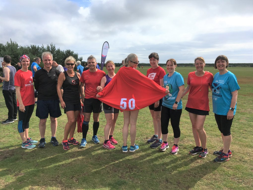 Photo shows a group of Footers with Pauline showing off the cape and Christine pointing to the 50 on it