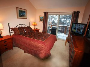 Master bedroom has a queen bed, TV, and balcony.
