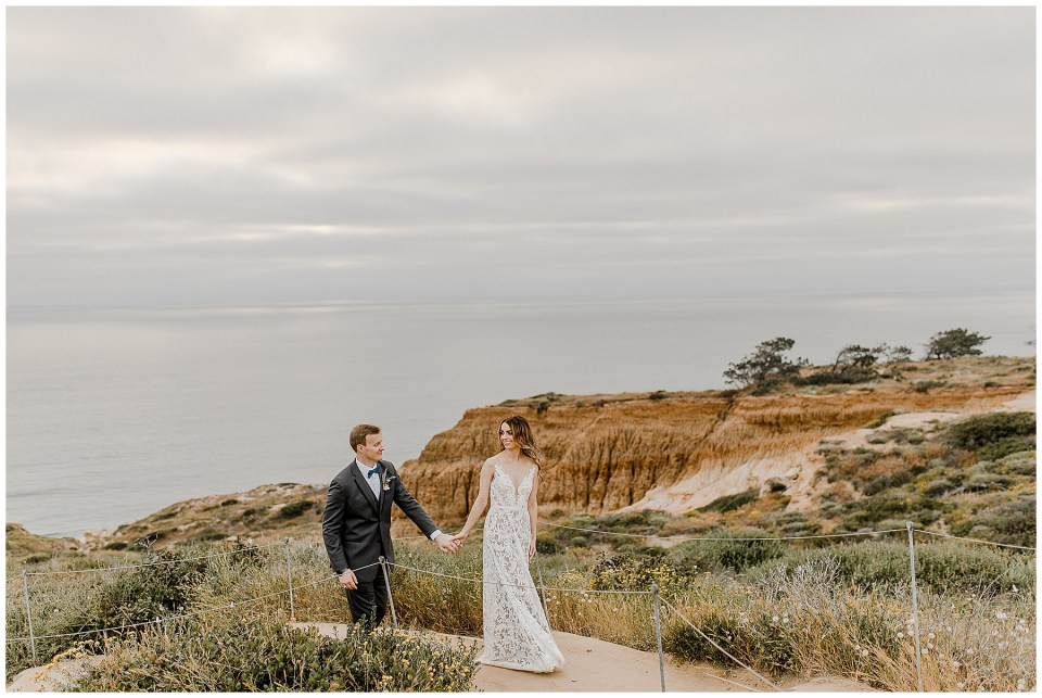 bride and groom stroll through torrey pines natural reserve