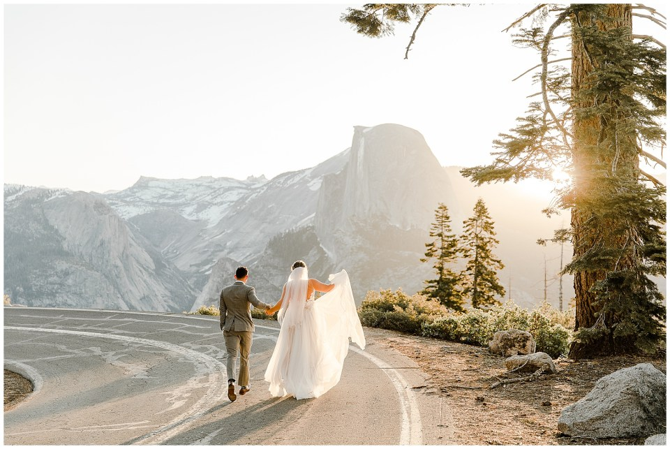 bride and groom walking on road in yosemite national park with half dome in the background