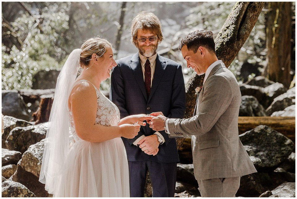 bride and groom exchange rings at bridal veil falls in yosemite